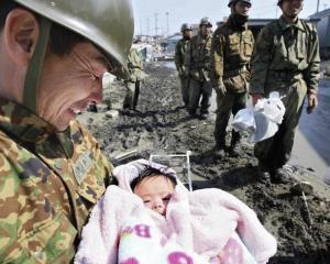 ▼石巻市で救出された赤ちゃん3月14日(AFP)
