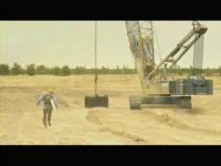 クレーン車から落下させた重石をシーソーの端に当て空に舞い上がる男