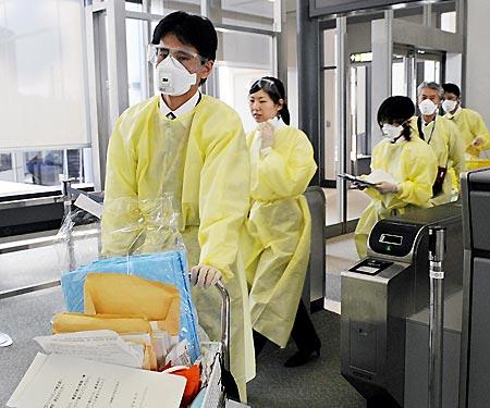 シカゴからの到着便の機内検疫を終えた検疫官=4月30日、成田空港