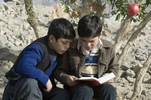 ハッサン(左)に本を読み聞かせるアミール