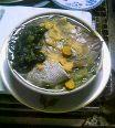 鯛の頭の酒蒸し。底が鯛、左の緑色は処理済菠薐草、黄色いのは生姜と生ウコン、右端でヘタっているのがおぼろ昆布。