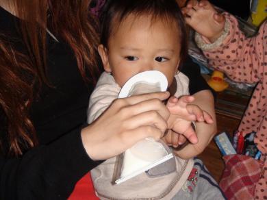 使い捨て哺乳瓶と調乳済みミルクを飲む赤ちゃん