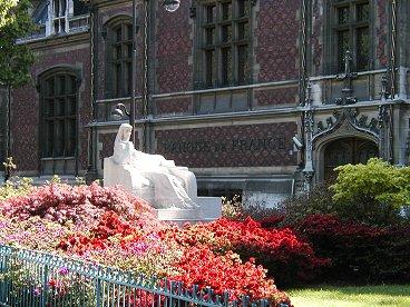旧フランス銀行前の花に埋もれたマリア像downsize