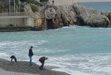 玉砂利の浜辺で石投げをする若者たちREVdownsize