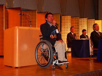 写真キャプション=スペシャルゲストとして登場した狩野亮氏。同氏はマルハンの契約社員で、第10回冬季パラリンピック・バンクーバー大会で金と銅メダルを獲得した