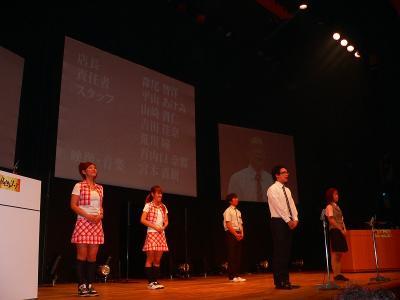 写真キャプション=決勝大会の舞台上でプレゼンを行う「駅前ペリカン」チーム