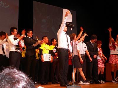 写真キャプション=日本一に決定した喜びを場内の観客に伝える「駅前ペリカン」のスタッフ