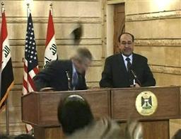 靴をかわすブッシュ米大統領